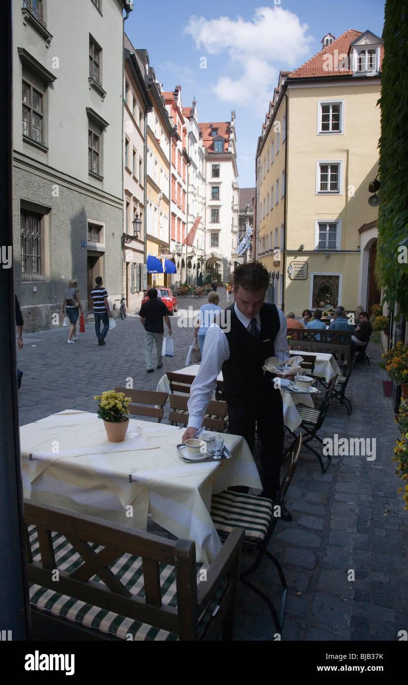 Waiter preparing a street table. Platzl. Munich, Germany - Stock Image