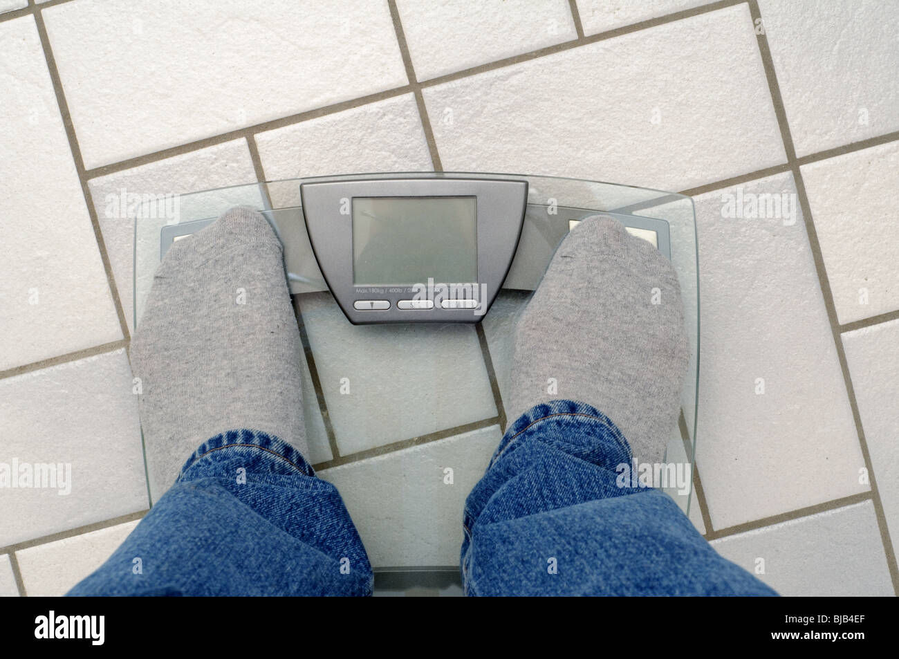 The jeans and socks of a man standing on a scale. Text window on scale free for your own text. - Stock Image