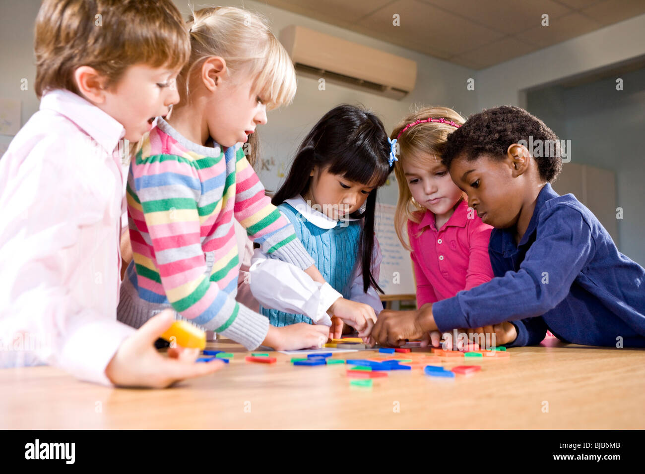 Preschool Children Working Together On Puzzle Stock Photo