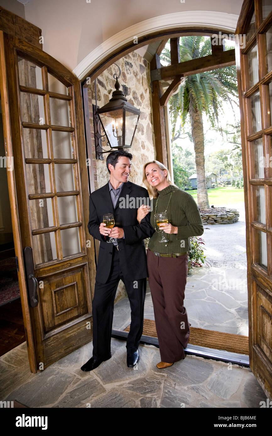 Interracial couple drinking wine walking through front door of Stock