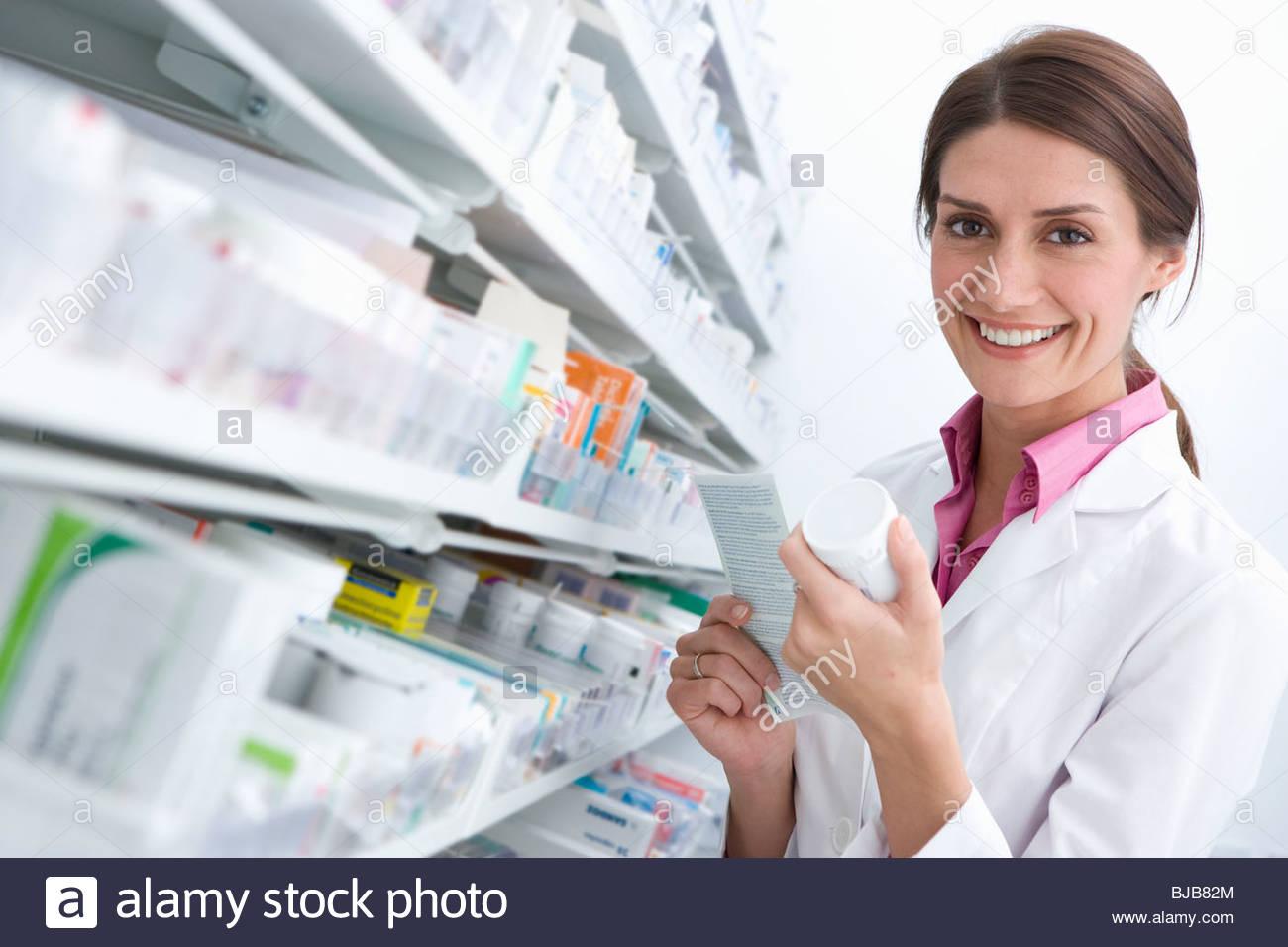 Pharmacist reading medicine bottle in pharmacy - Stock Image