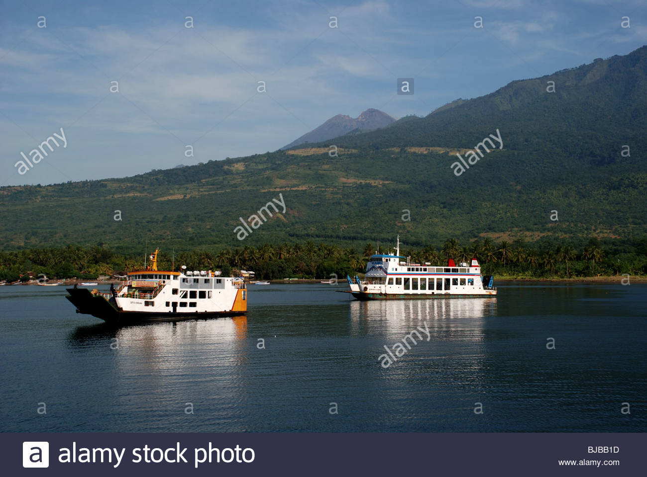 Two ferryboats in harbour with Gunung Rinjani volcano in background Kayangan Labuan Lombok Lombok Timur NTB Indonesia - Stock Image