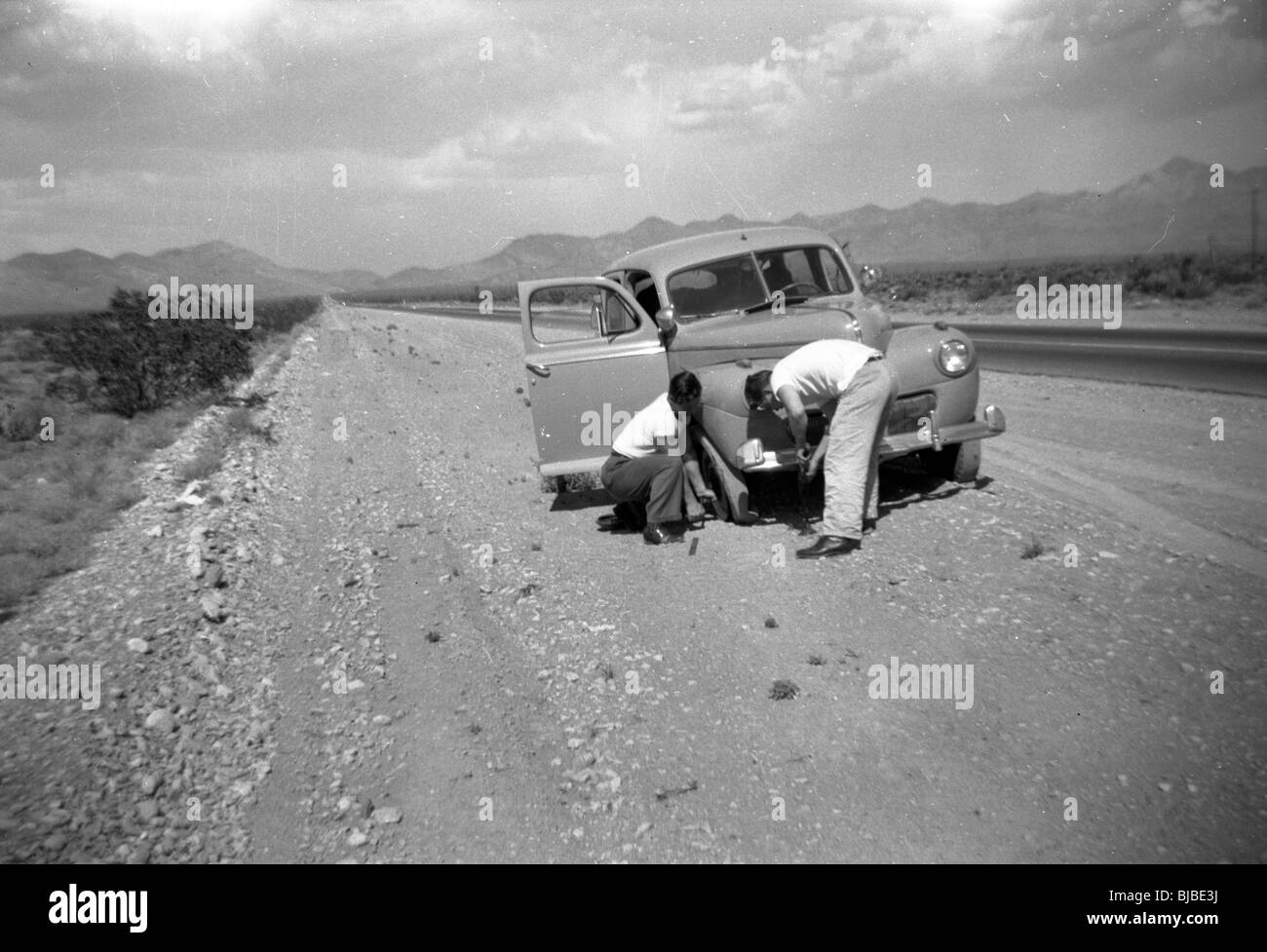 Two travelers change a flat tire in the American Southwest during the 1940s. car travel highway mountains desert - Stock Image