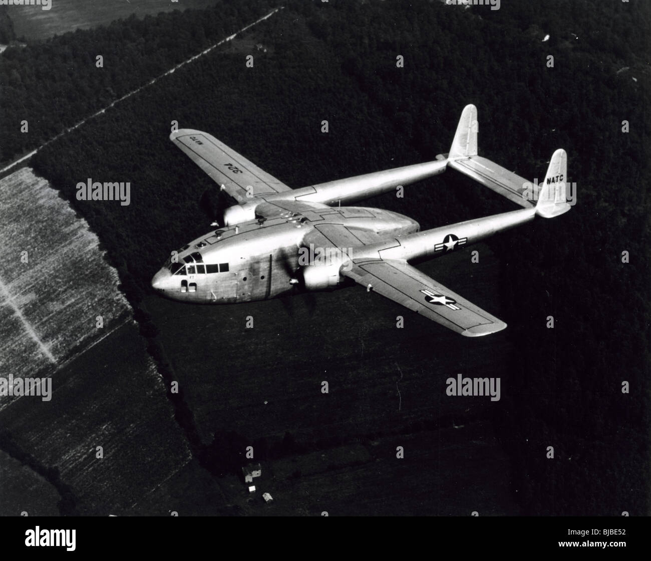 Korean War era Fairchild C119 flying boxcar twin engine cargo airplane flies on a mission. American military transport - Stock Image