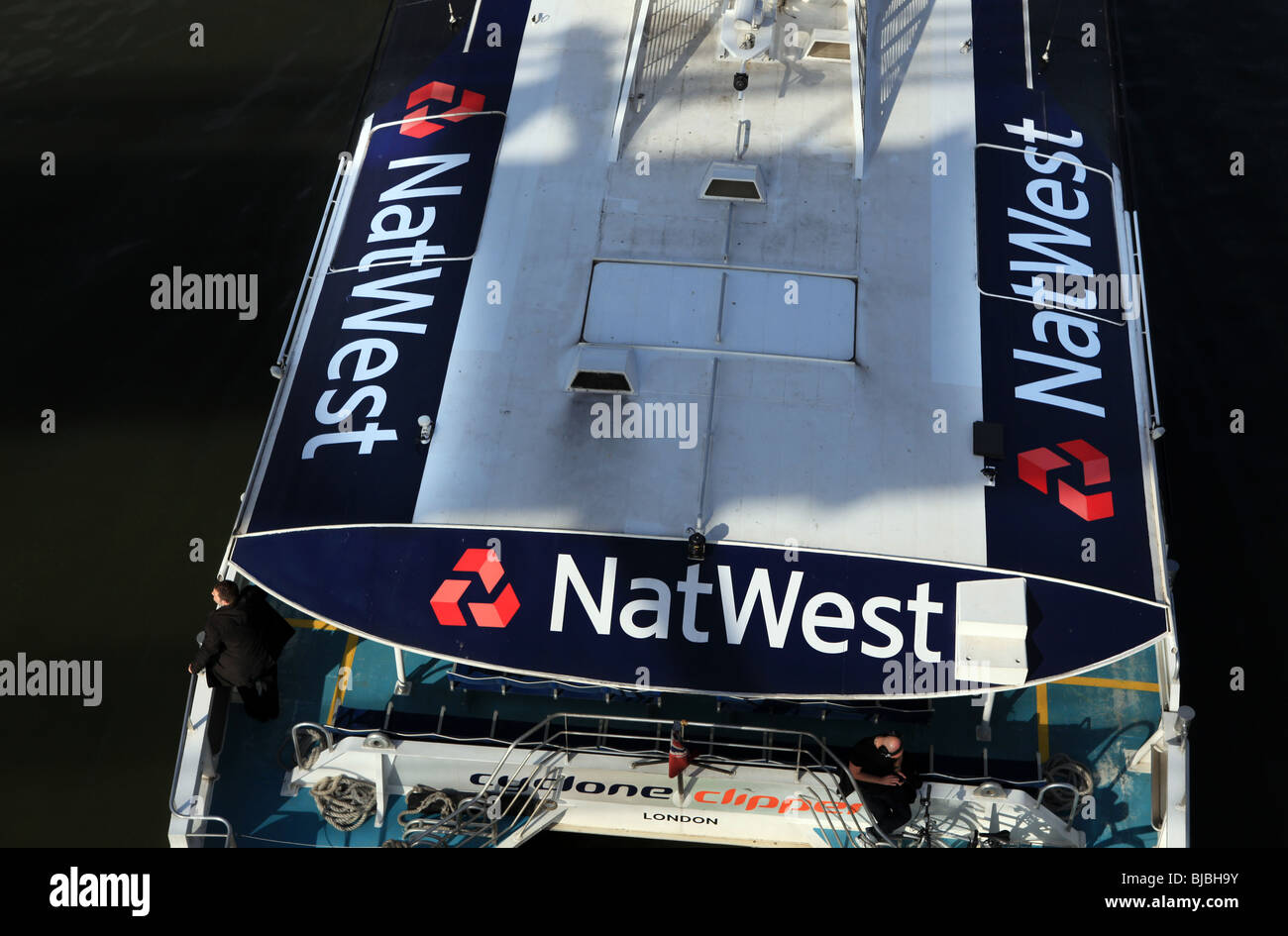 A ferry boat with the Nat West Bank logo travels down the river Thames in London - Stock Image