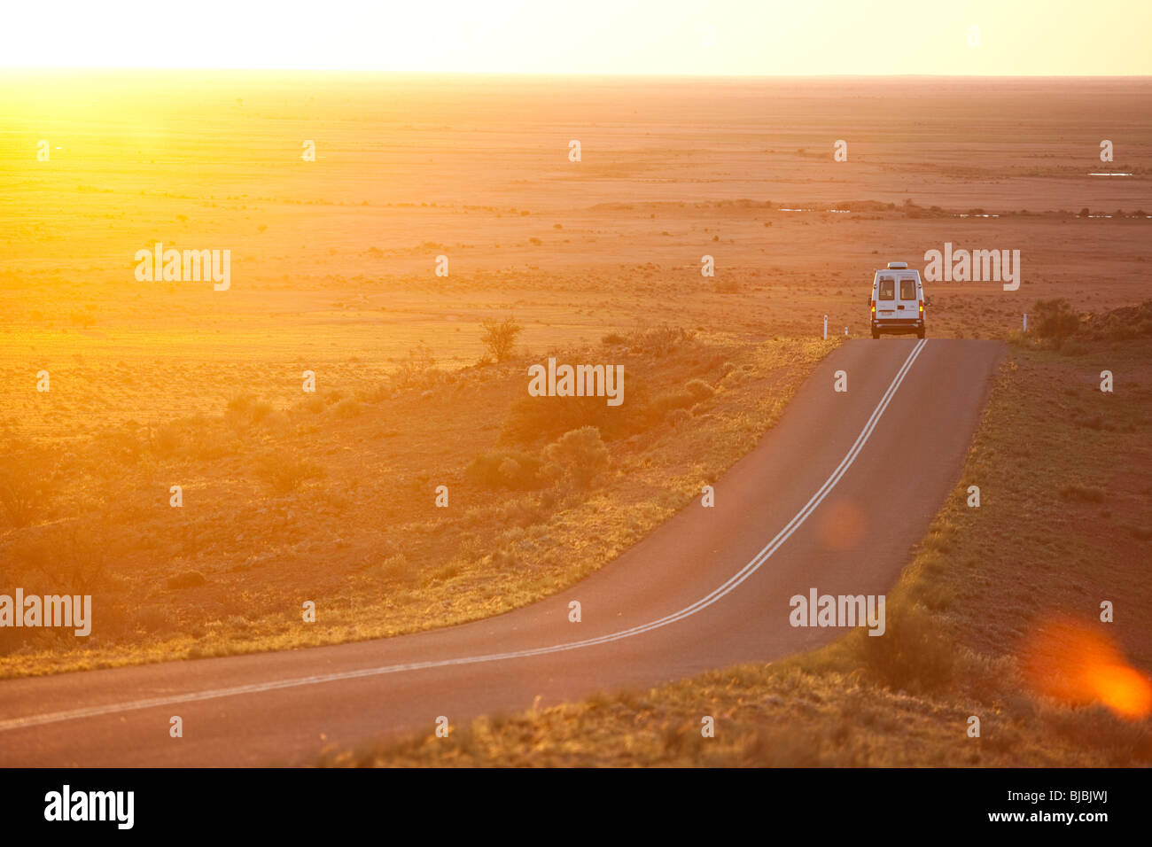 A camper van driving through Australian outback, Silverton NSW, Australia - Stock Image