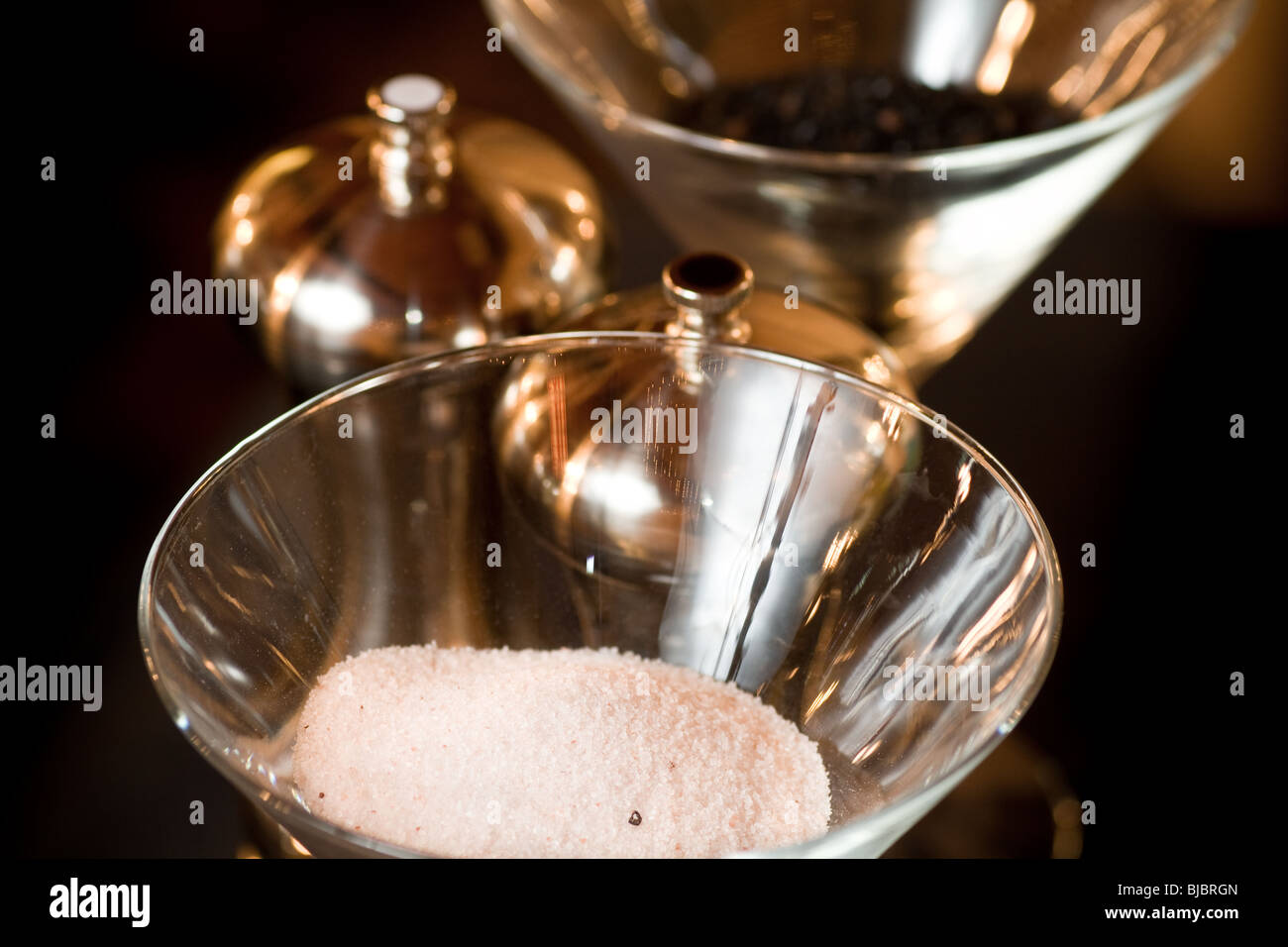 Salt and pepper displayed in open glasses, with metal pepper mills present. - Stock Image