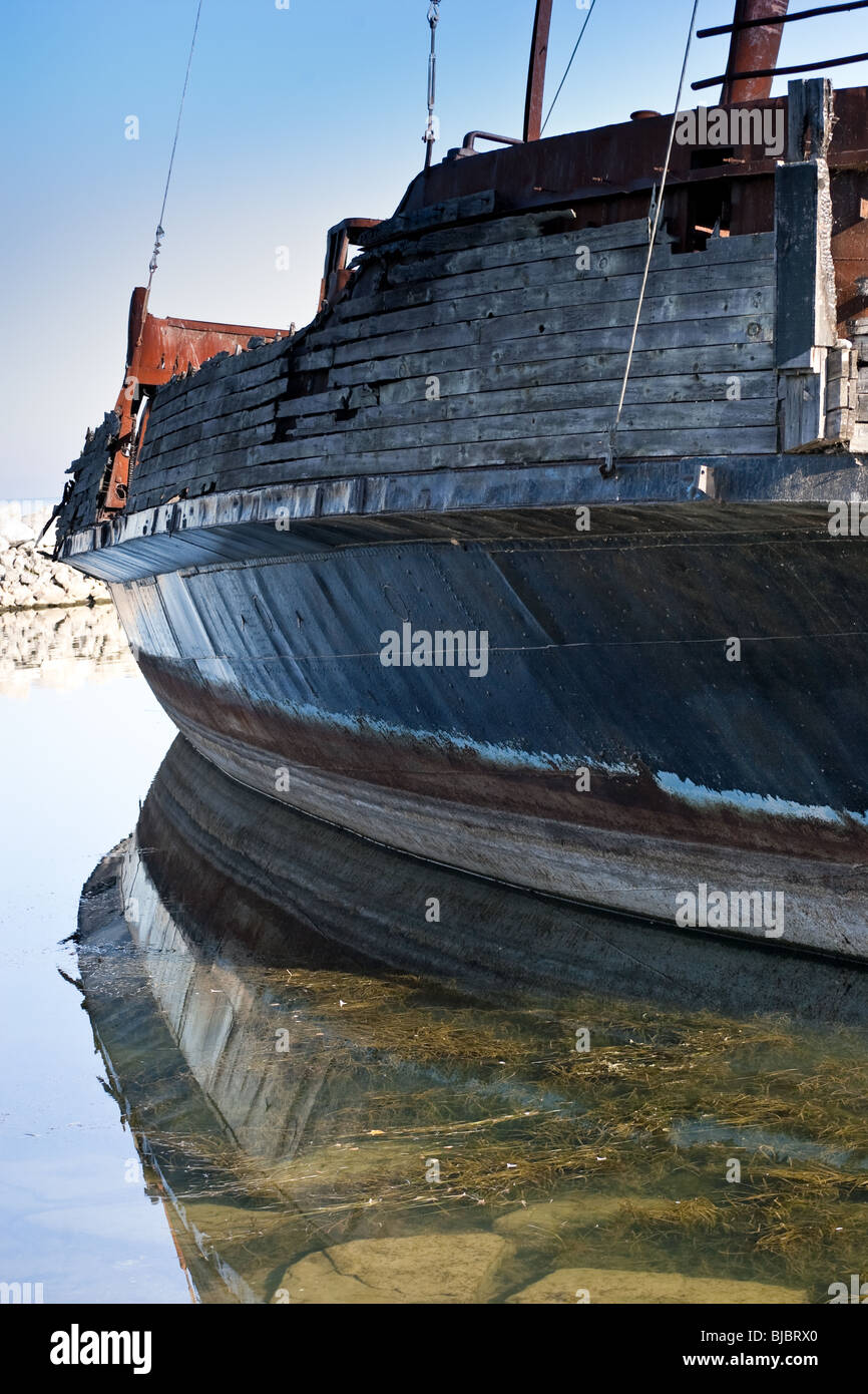 The side of an old pirate ship, reflecting off the still water. - Stock Image