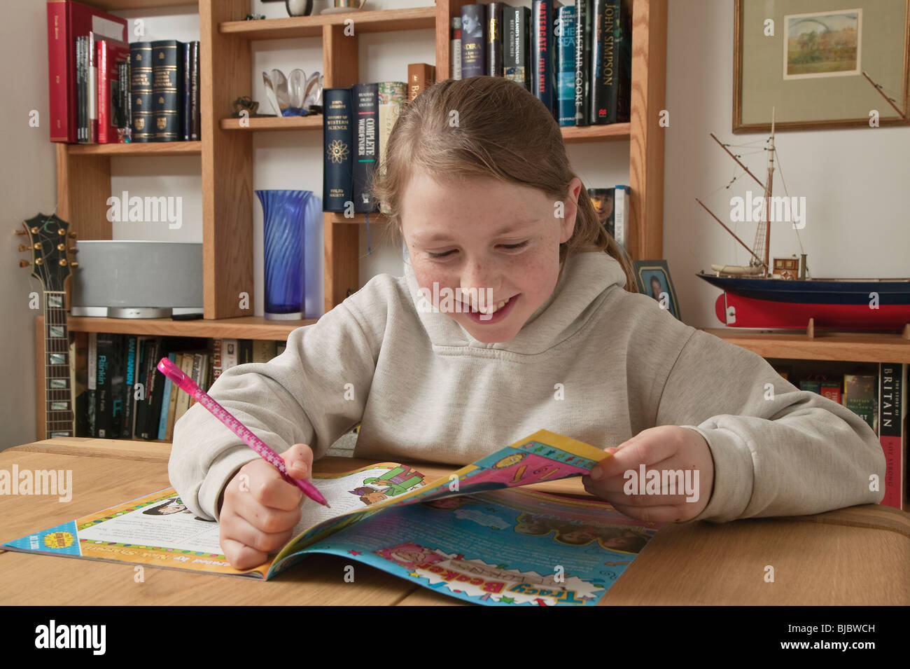 Ten year old girl with comic in front of bookshelves. - Stock Image