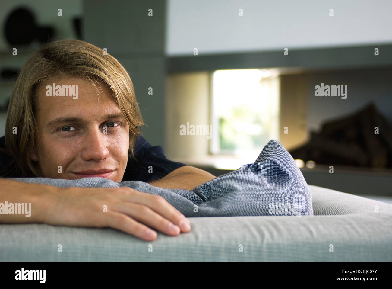 Man relaxing on sofa, smiling, portrait - Stock Image