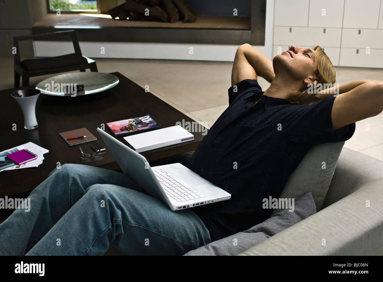 Man relaxing on sofa with laptop computer on lap - Stock Image