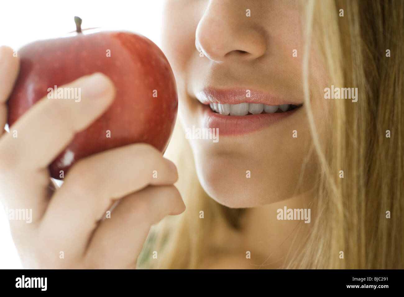 Young woman eating apple, close-up - Stock Image