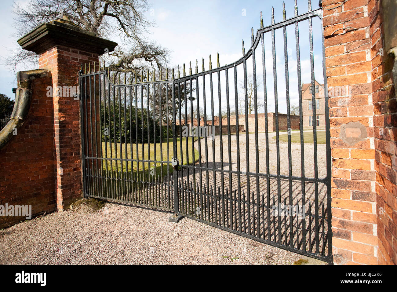 large closed and padlocked gates to grounds of a large house - Stock Image