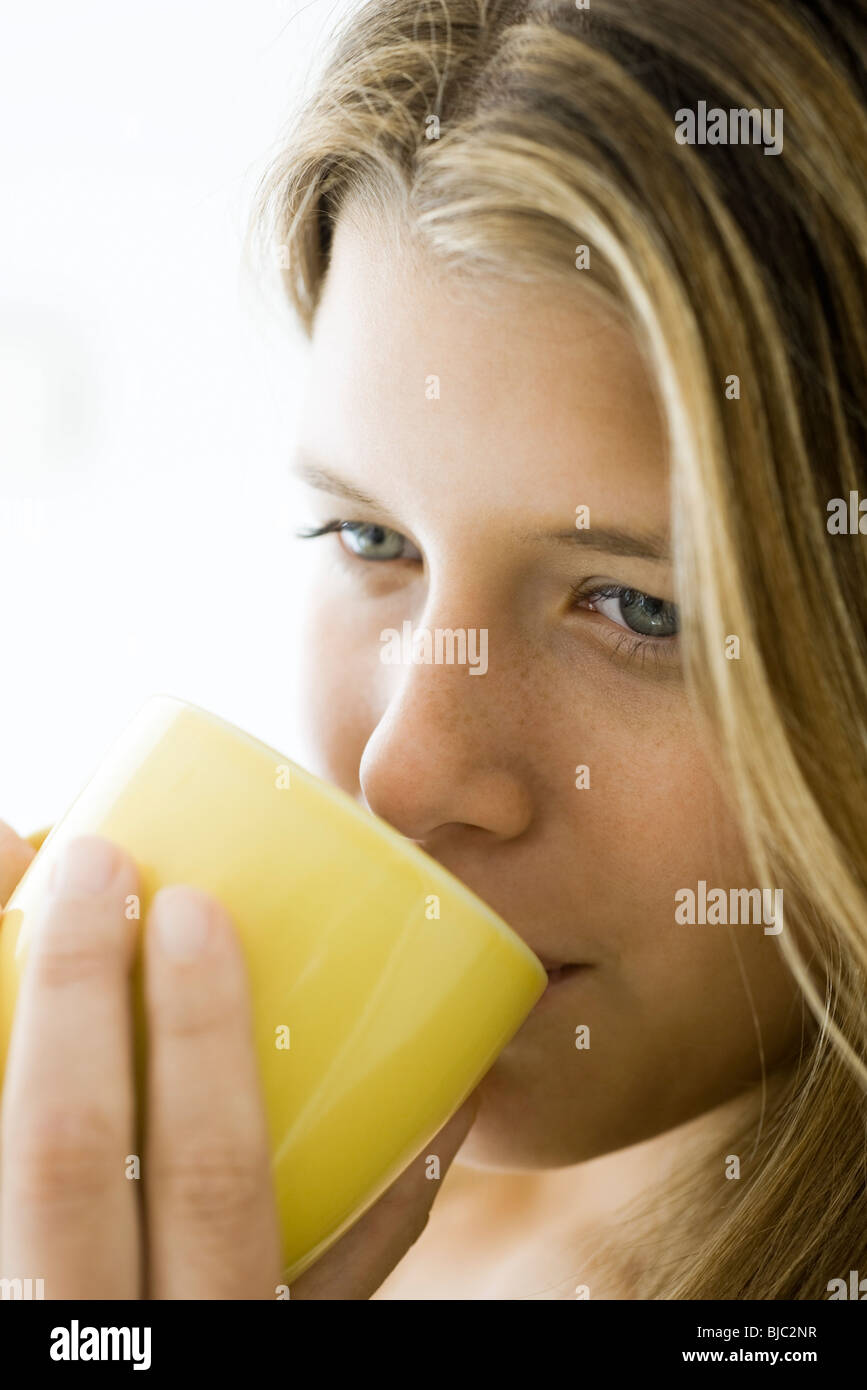Young woman enjoying cup of coffee, portrait - Stock Image