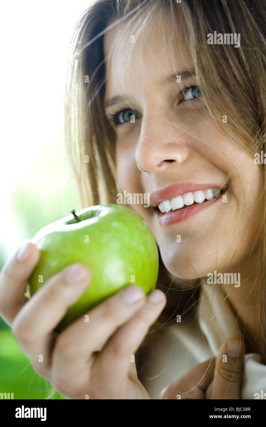 Young woman eating green apple - Stock Image