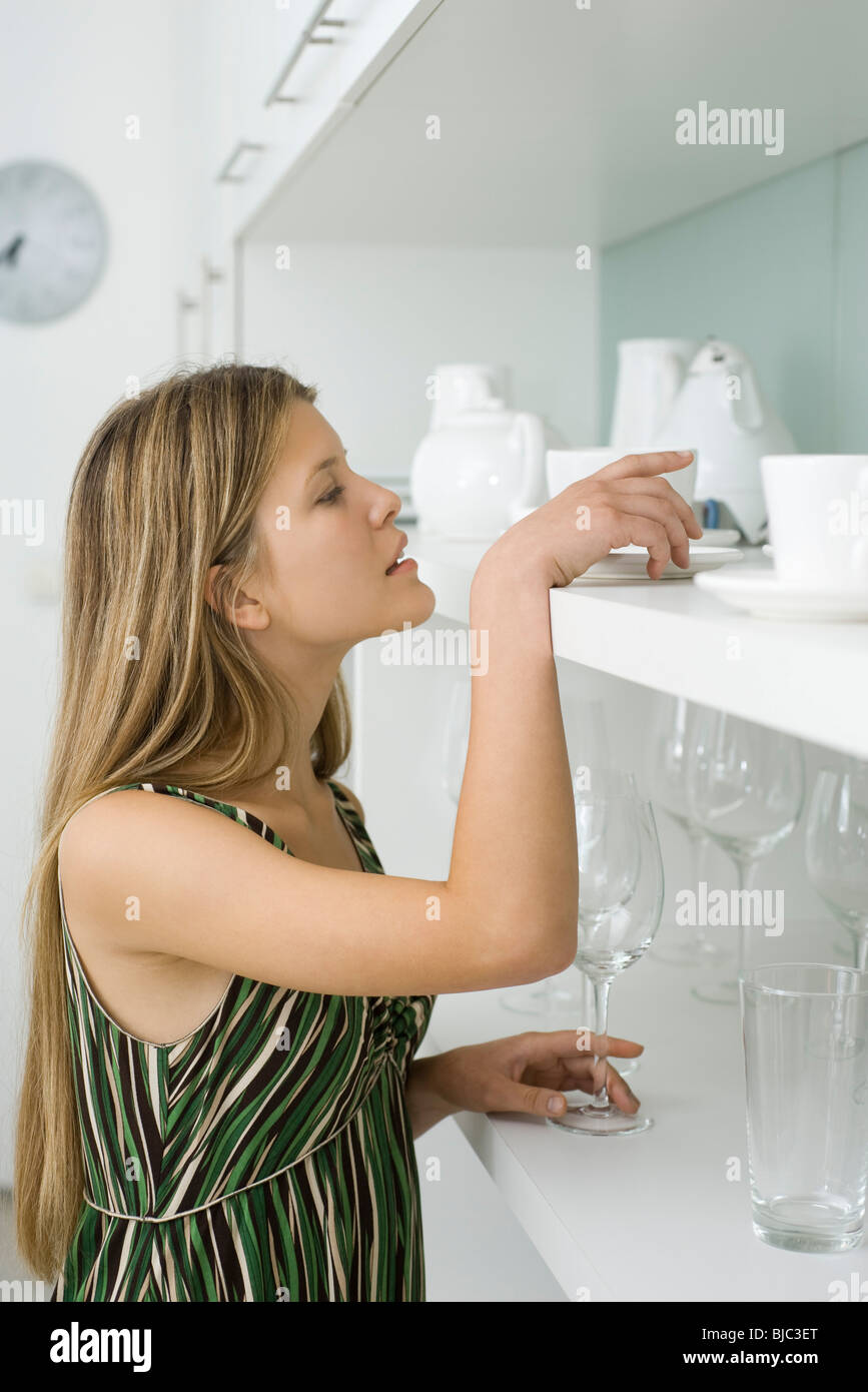 Young woman looking for dish stored on shelf - Stock Image