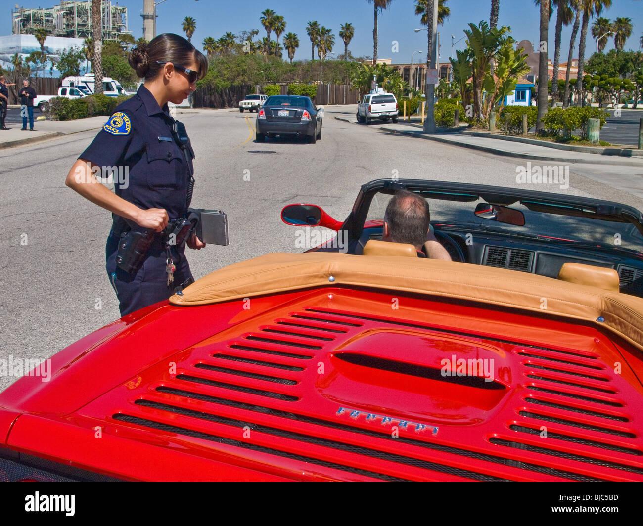 Female police officer at traffic stop, detains male Ferrari driver. - Stock Image