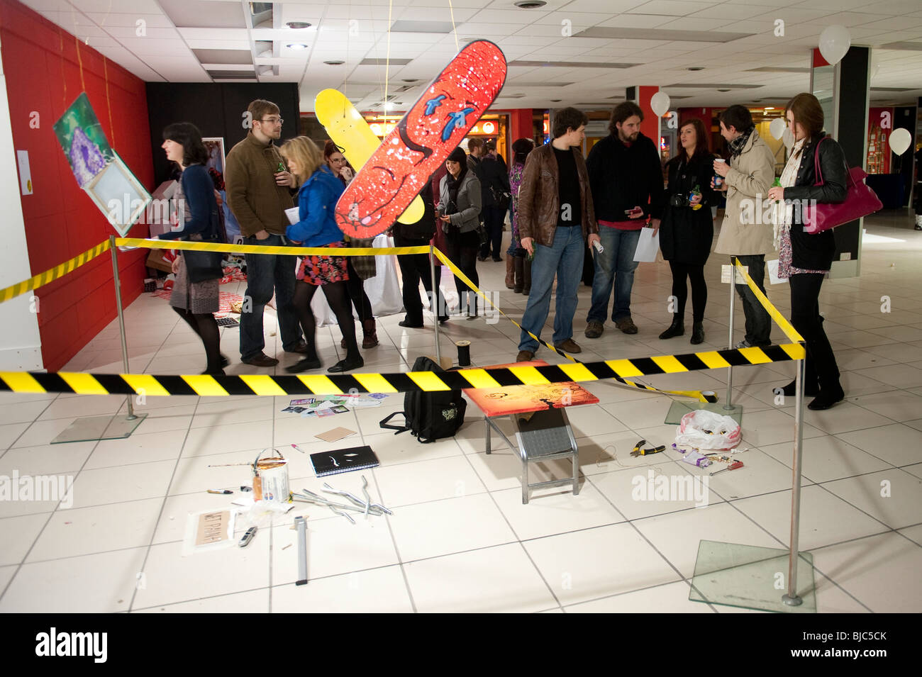People looking at art in a temporary one night only site specific installation exhibition gallery in an empty shop - Stock Image