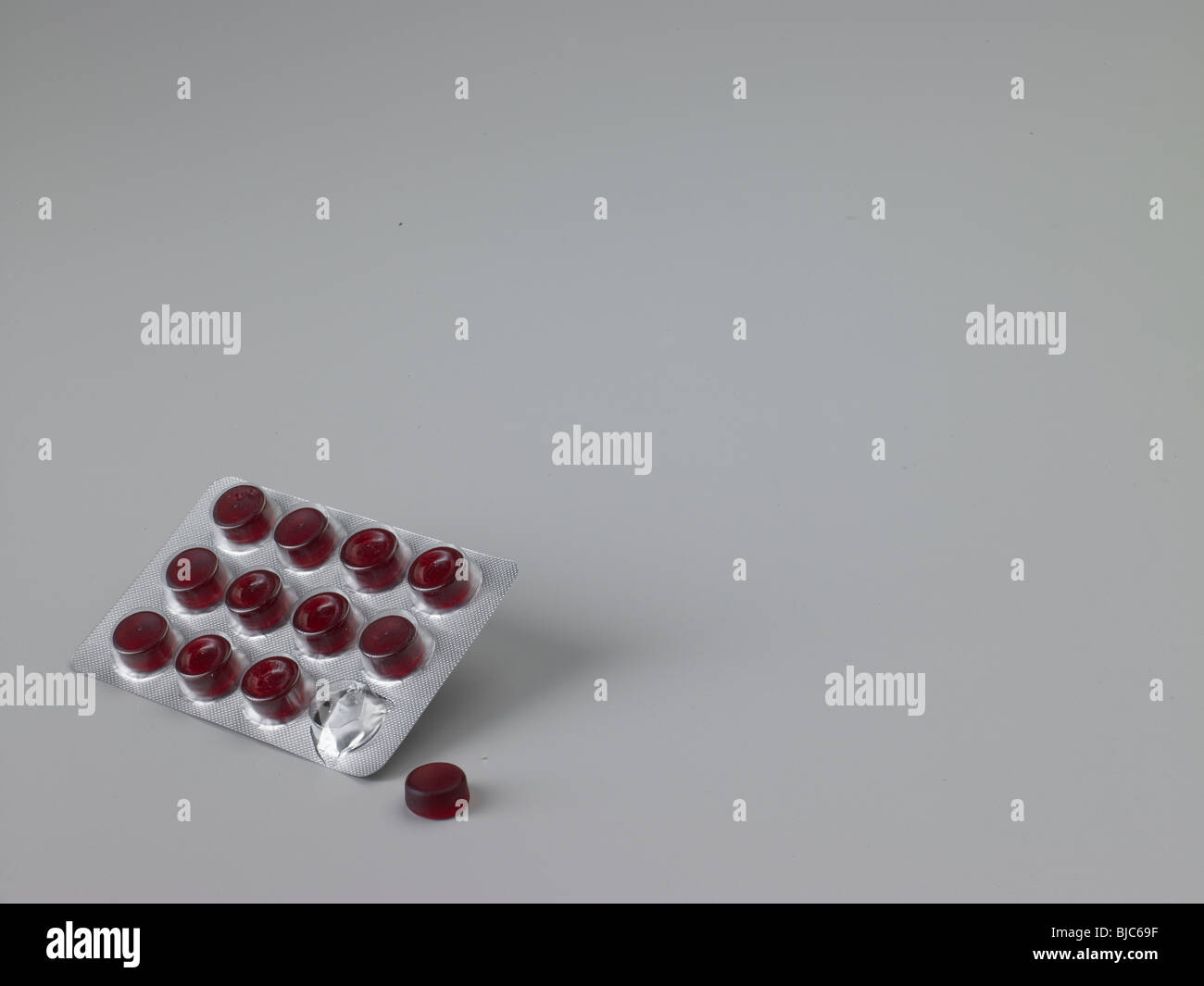 pharmaceutical tablets on grey background. Red  tablets in blister pack with one tablet out of packaging. medium - Stock Image