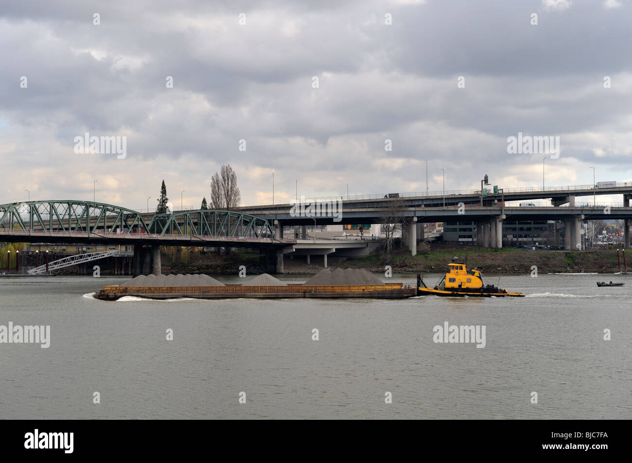 A river barge and tugboat on the Willamette River going under the Hawthorne Bridge, Portland, OR 100304_34896 - Stock Image