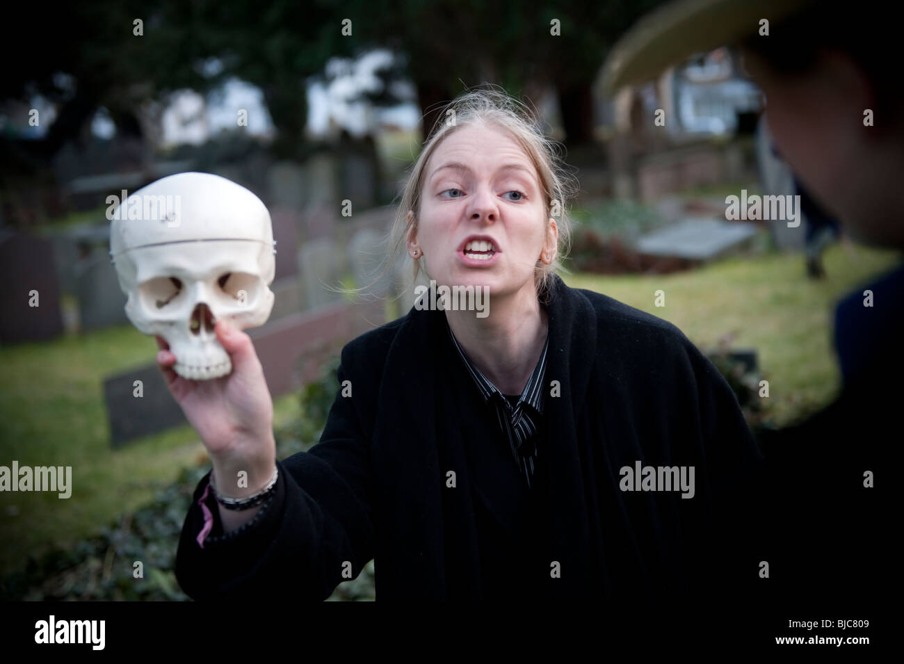 A Women student at Aberystwyth University holding a skull performing the graveyard scene ('Alas, poor Yorick! - Stock Image