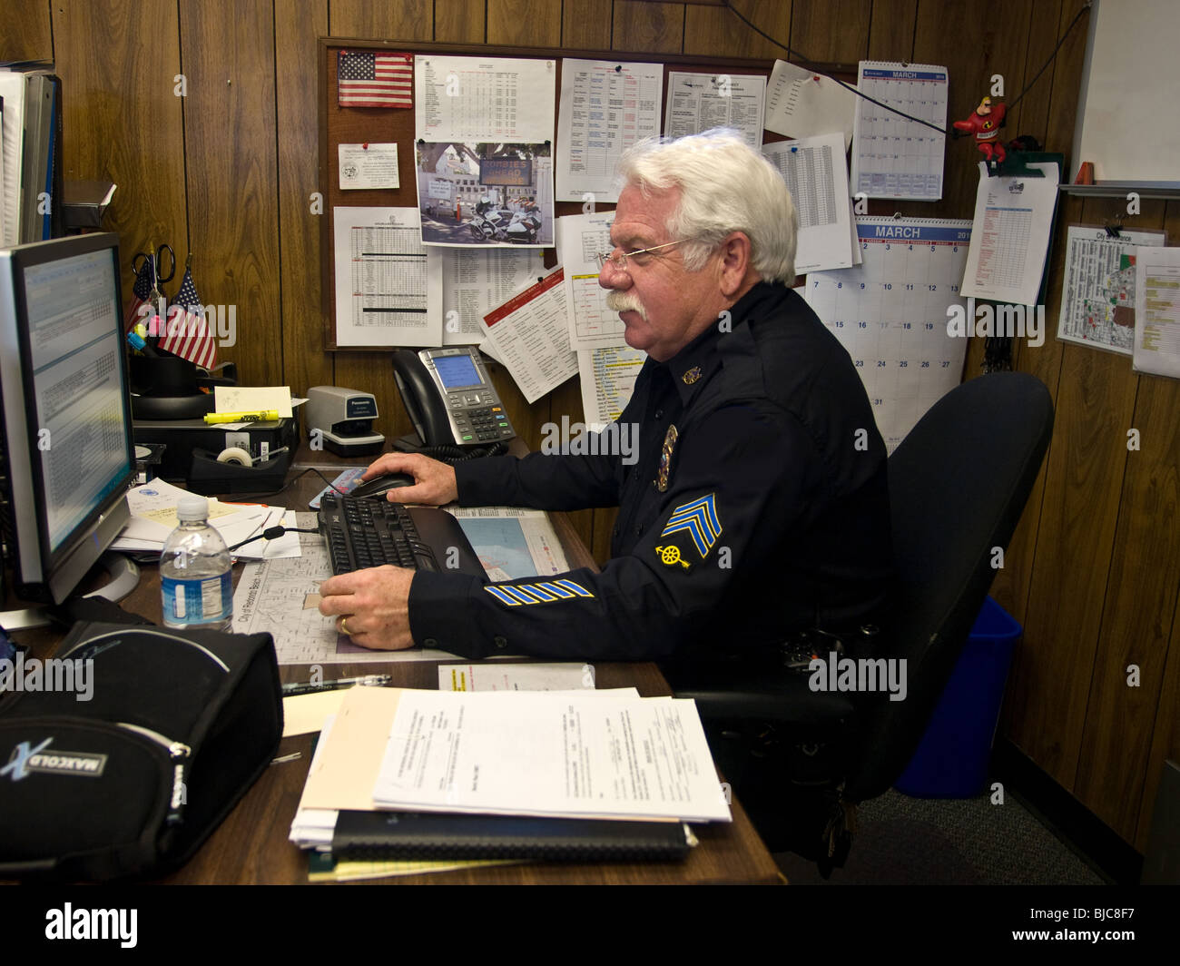 Senior police Sargent at work at his desk Stock Photo