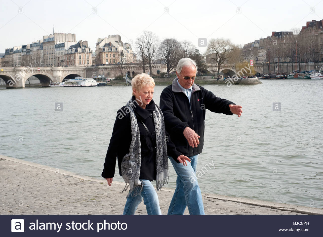 Senior couple walking along Seine river, Paris, France, Stock Photo