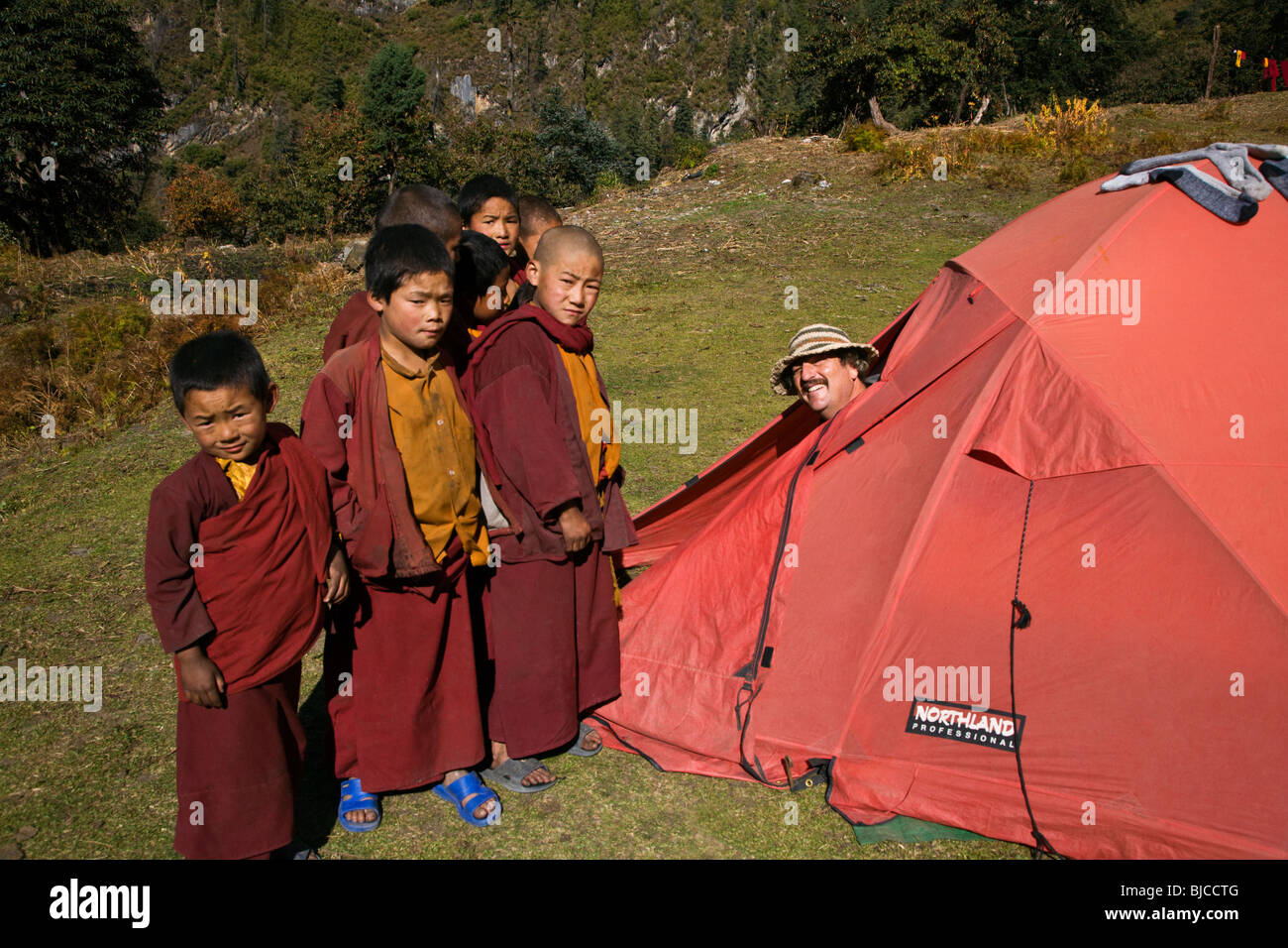 Craig Lovell pops out of his tent to visit with young monks at a remote TIBETAN BUDDHIST MONASTERY - NEPAL HIMALAYA - Stock Image