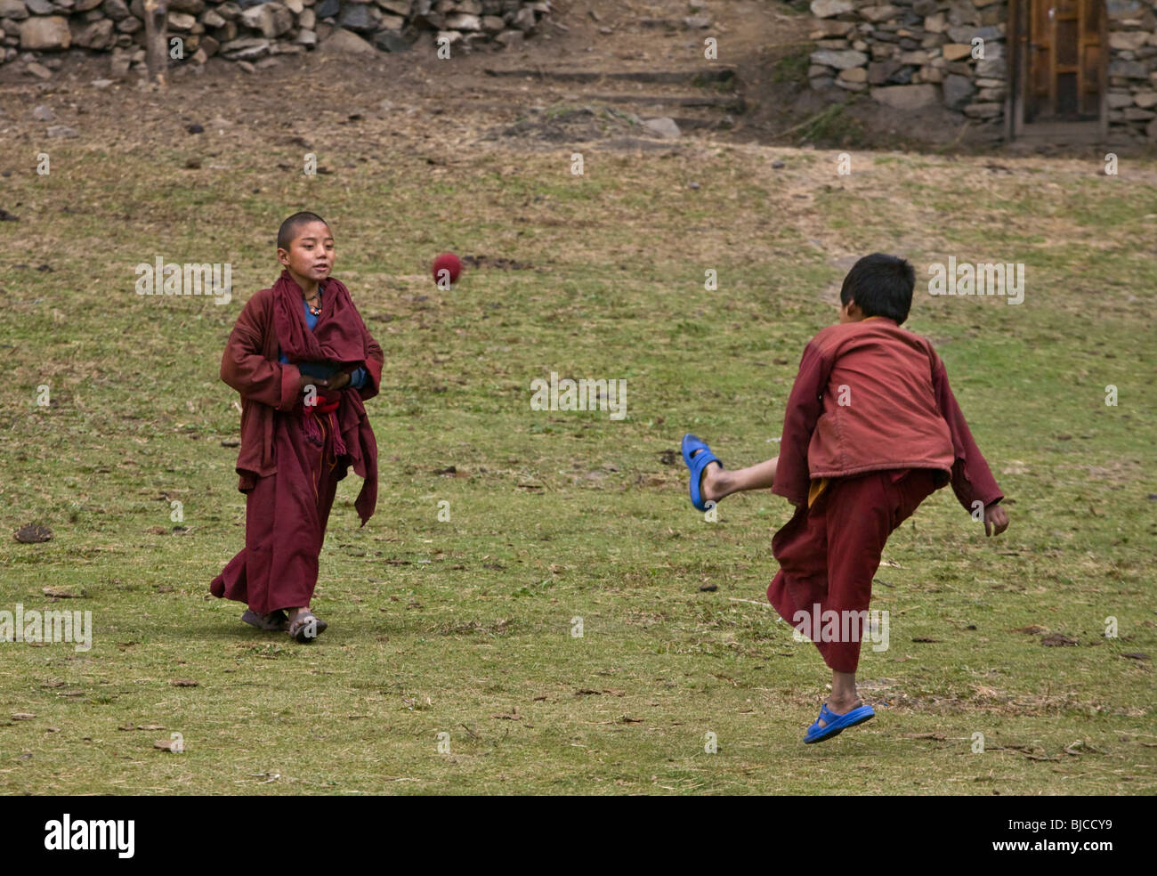 Young MONKS play soccer at a remote TIBETAN BUDDHIST MONASTERY - NEPAL HIMALAYA Stock Photo