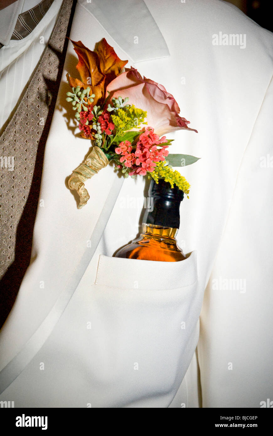 Bottle of liquor in grooms pocket just after a wedding - Stock Image