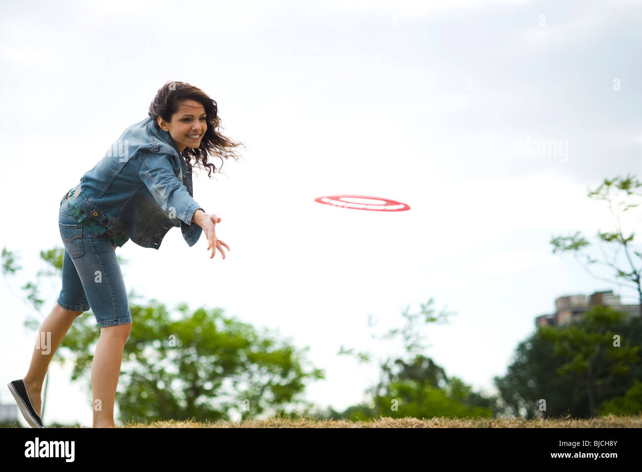 Woman throwing flying disc at park - Stock Image