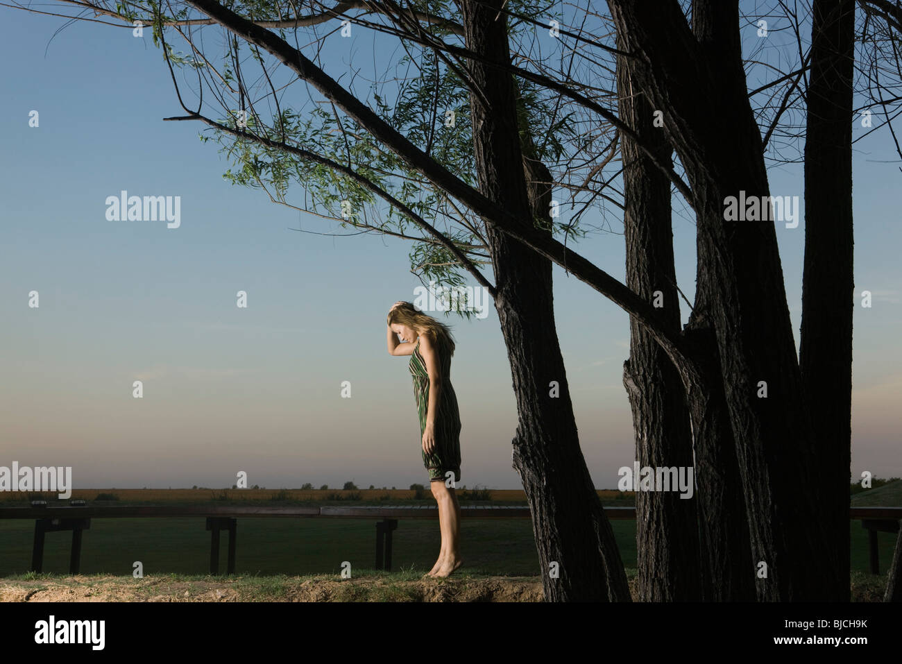Woman standing on tiptoes outdoors, holding head and looking down - Stock Image