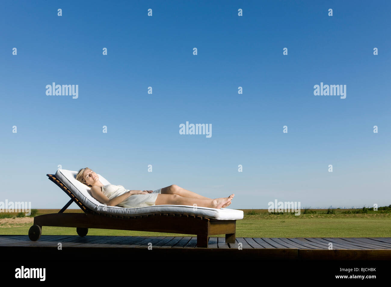 Woman napping on lounge chair on deck - Stock Image