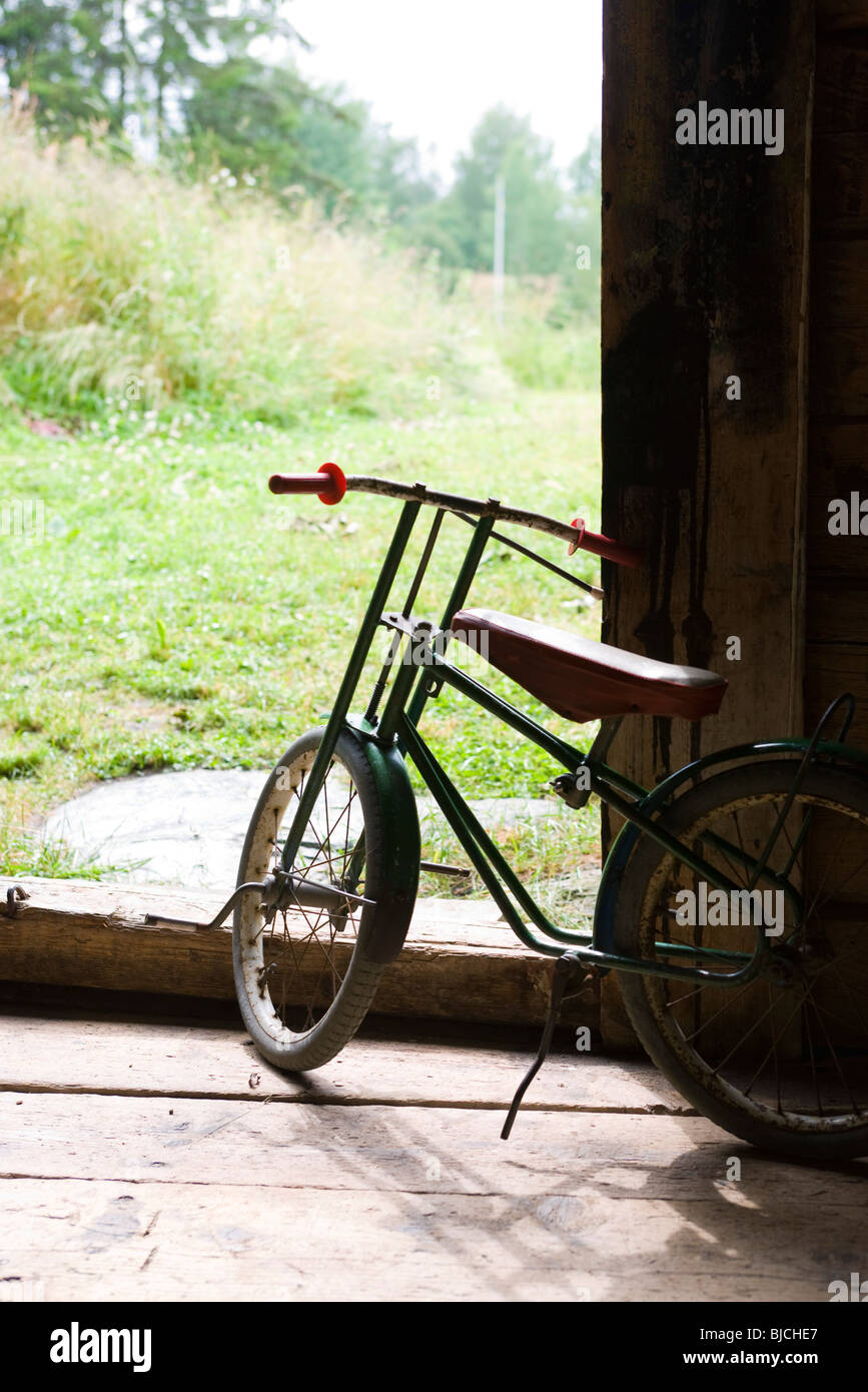 Child's bicycle stored in garage - Stock Image