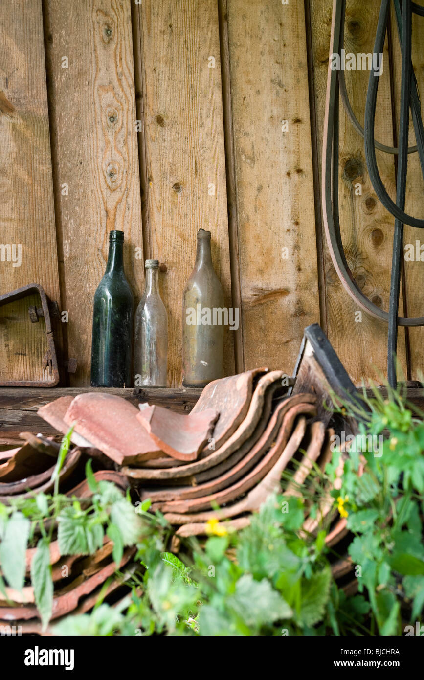 Old glass bottles, broken clay tiles stacked by wall outdoors - Stock Image