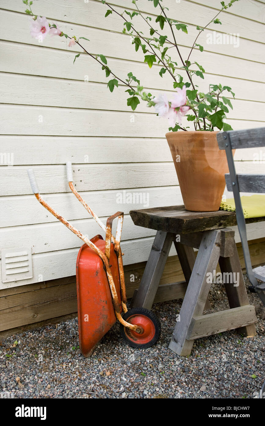 Child's toy wheelbarrow leaning against side of house - Stock Image