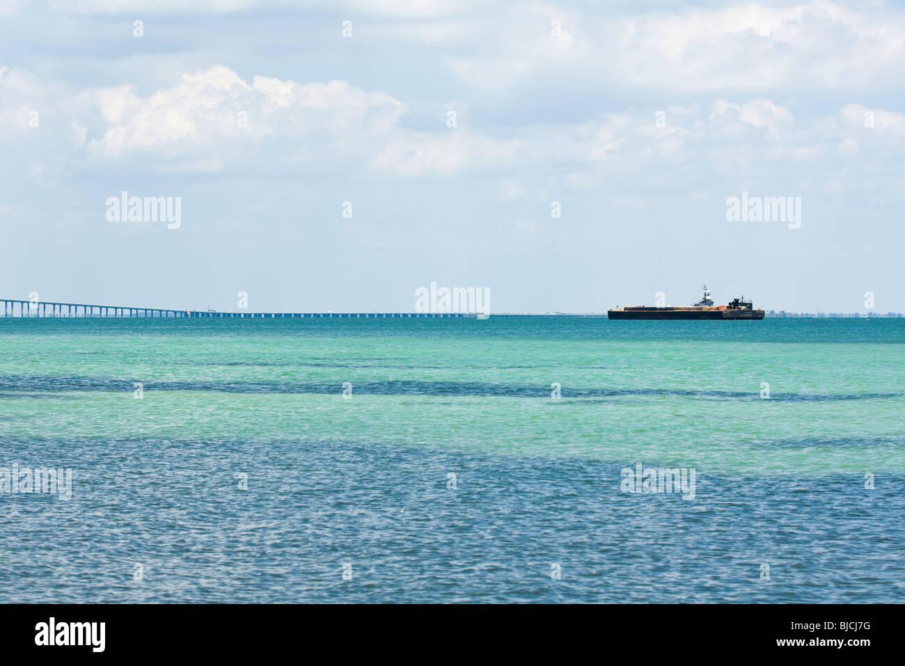 Seascape with barge on horizon - Stock Image