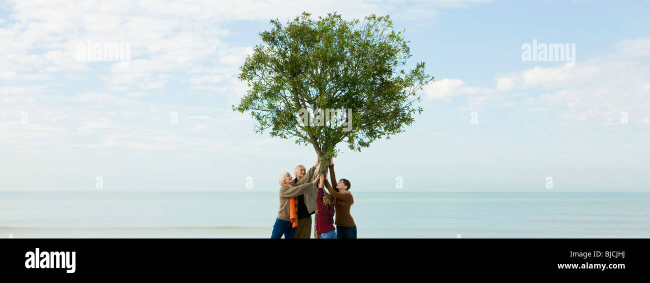 Ecology concept, group of people supporting tree together - Stock Image