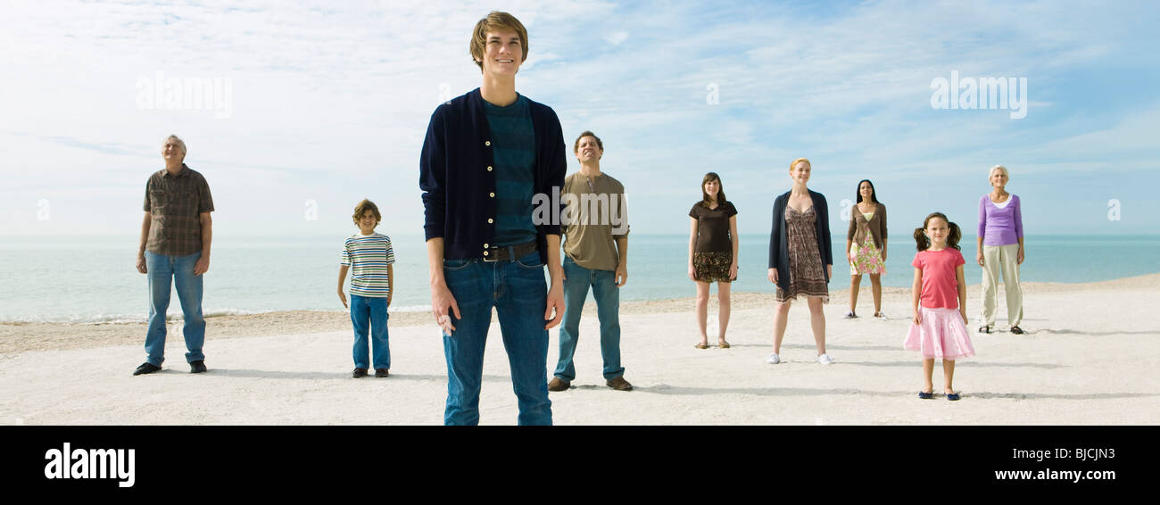 Group of individuals standing on beach, smiling optimistically - Stock Image