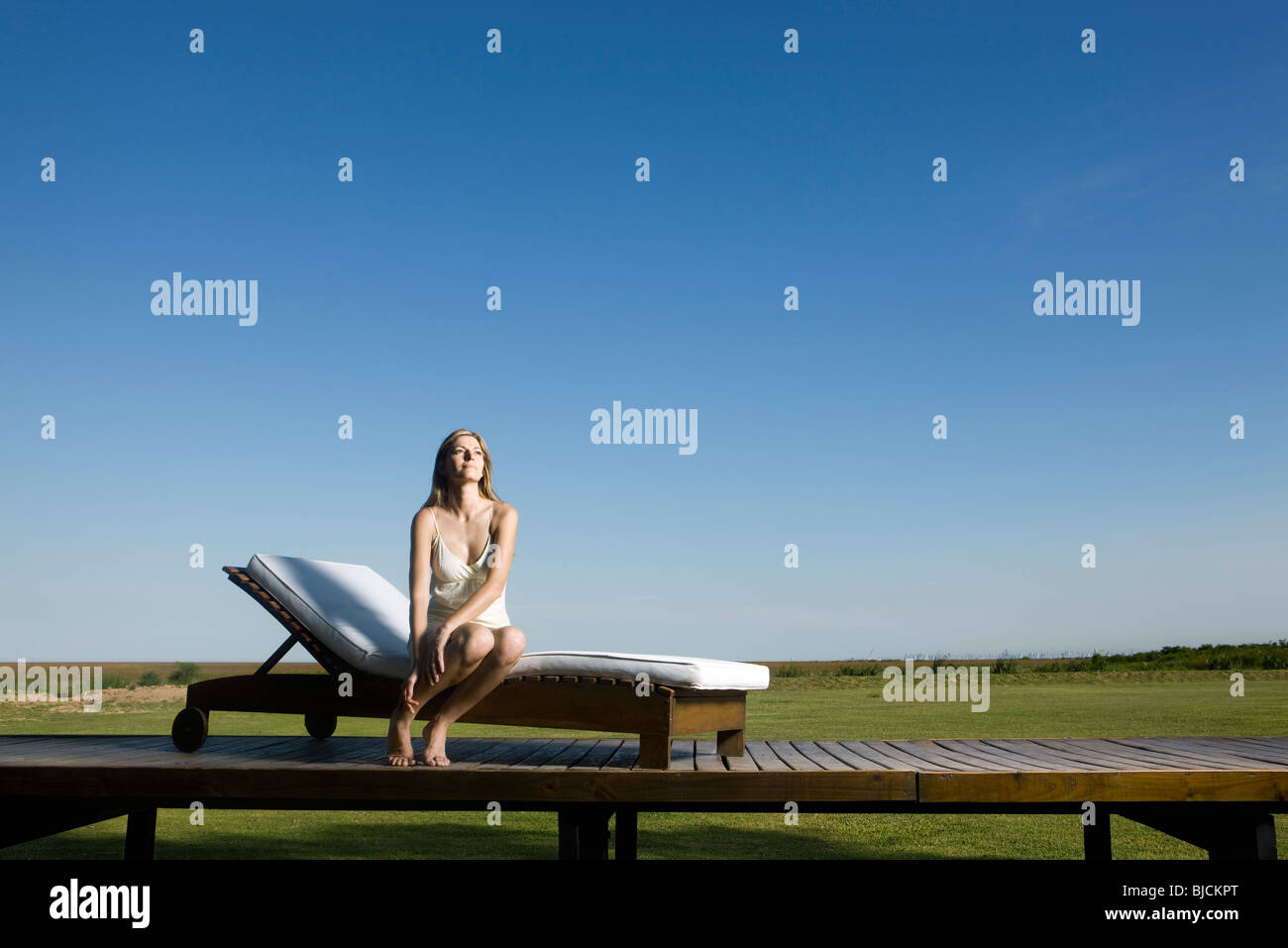 Woman sitting on lounge chair outdoors, looking up dreamily - Stock Image