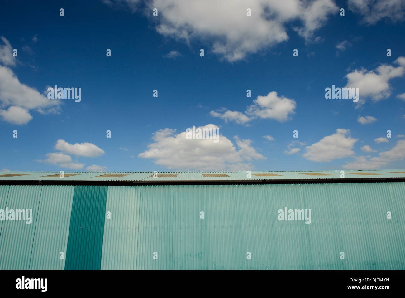 Blue painted corrugated iron shed, with blue sky and white clouds - Stock Image