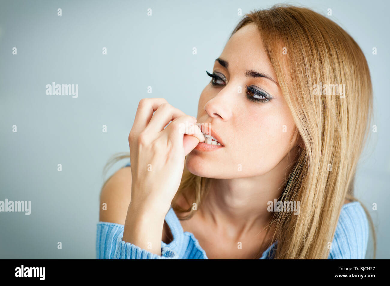 portrait of 30 years old woman biting her fingernails on cyan background. Horizontal shape, Copy space - Stock Image