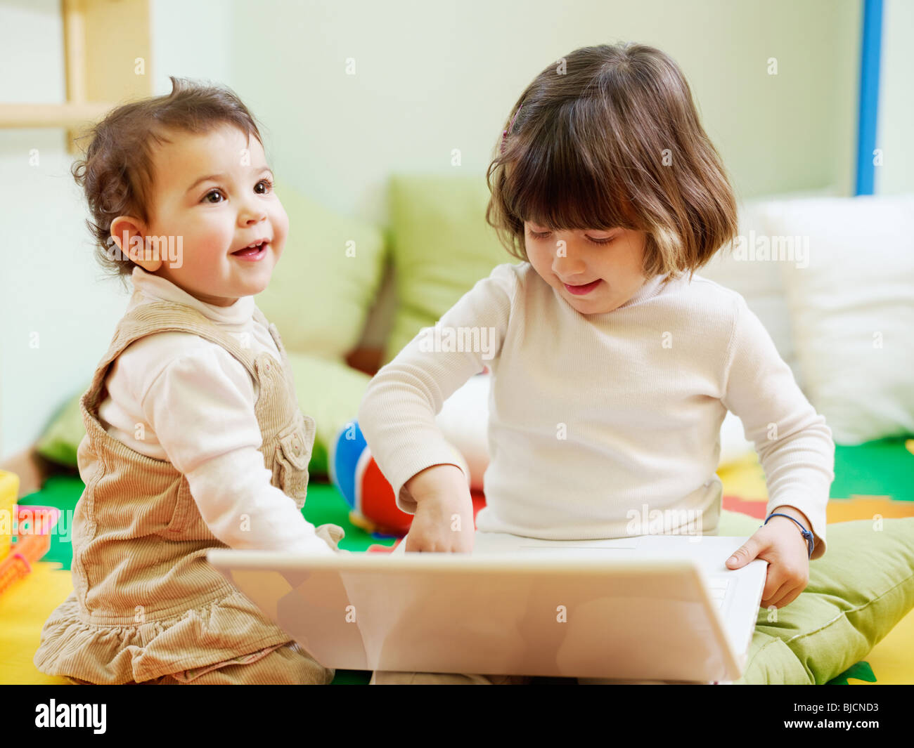 female toddler and 2-3 years old girl playing with pc in kindergarten. Horizontal shape - Stock Image