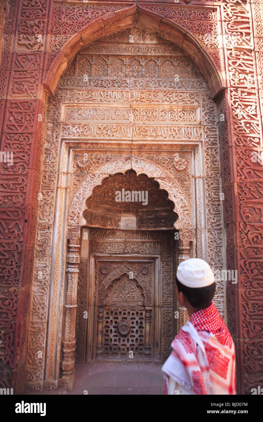 a6e8449dcca4 Muslim boy watching Islamic Ornamentation of Quran inscription carved on Qutab  Minar   Indo-Muslim
