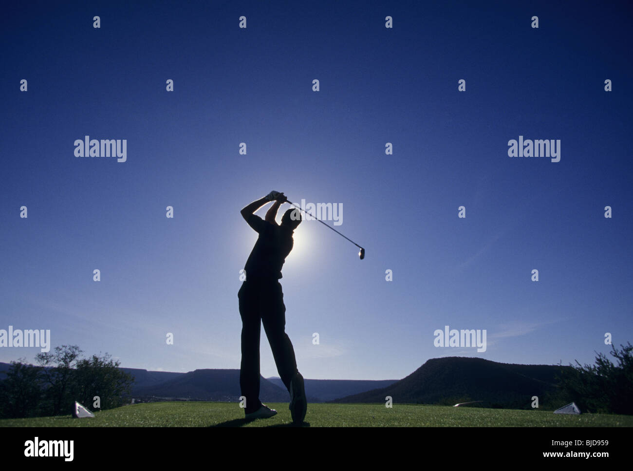 Silhouette of golfer teeing off on golf course - Stock Image
