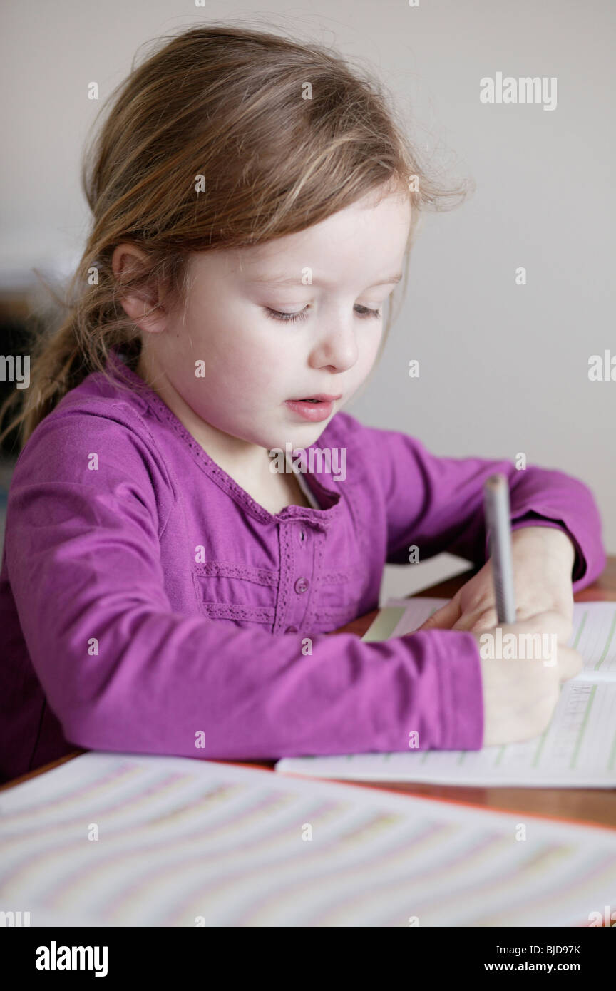 A little girl practices writing - Stock Image