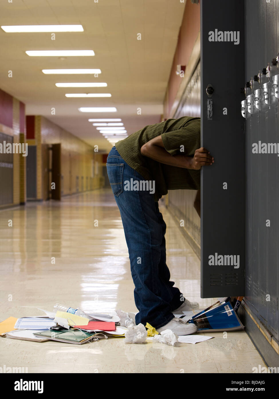High School student cleaning out his locker. - Stock Image