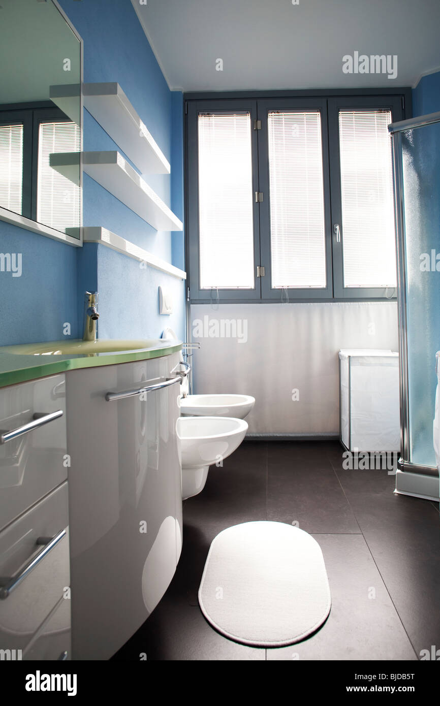 Modern white cabinets shiny polished in bathroom belonging to a studio apartment Stock Photo