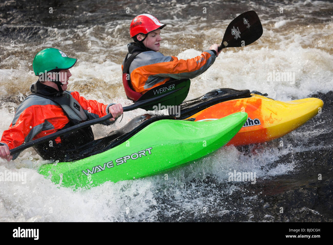 Two kayakers kayaking in white water on Tryweryn River. National Whitewater Centre, Frongoch, Gwynedd, North Wales, - Stock Image