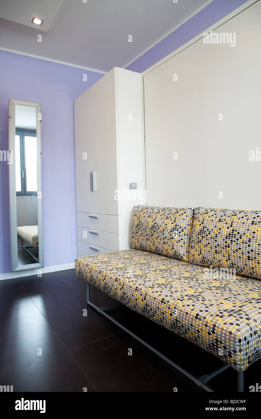Detail of a studio apartment with wardrobe sofa and murphy bed hidden behind white wall - Stock Image